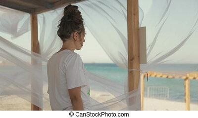 Young girl yogi meditating near the sea in the gazebo