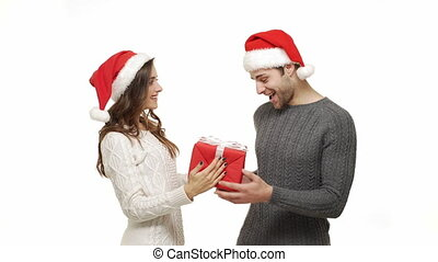 Young girlfriend close her boyfriend eyes and surprise her boyfriend with big red present for Christmas.