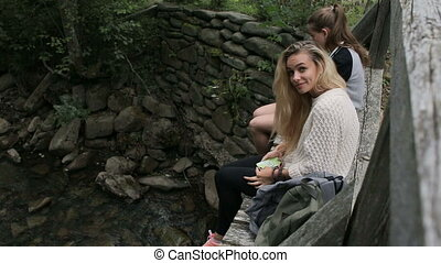 Young girls are sitting on a bridge across a mountain river