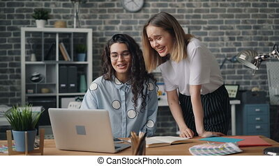 Young girls colleagues talking and laughing looking at laptop screen in office