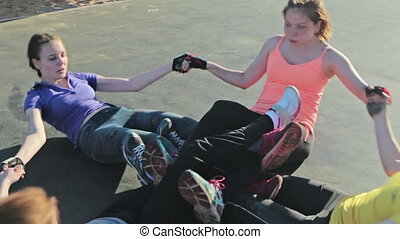 Young girls doing sit-ups exercising together