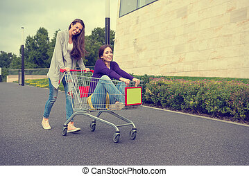 Young girls have fun with the shopping trolley