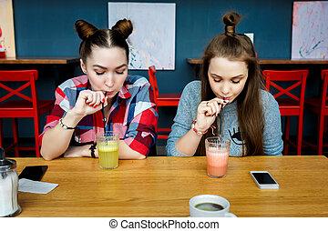 Young girls having fun in a cafe bar