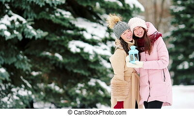 Young girls holding Christmas candlelight outdoors on beautiful winter snow day and warm their hands