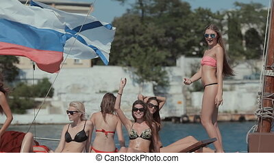 Young girls in bikini dancing and having fun on a yacht -...