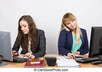 Young girls in the office, one works in the computer, the other on the phone and looking at the screen