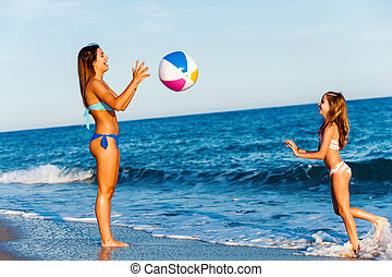 Young girls playing with ball on beach.