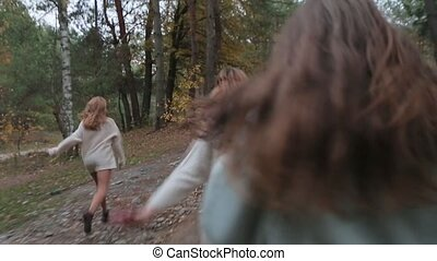 Young girls run in the coniferous forest