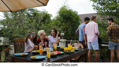 Young Girls Sitting At Table Taking selfie Photo While Men Group Cooking Barbecue Friends Gathering On Summer Terrace Talking People Communication