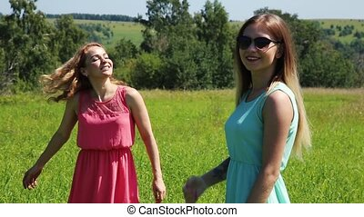 young girls spinning on a green grass, girlfrend in nature. slow motion