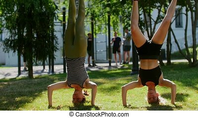 Young girls stand on their heads with all body weight in the...