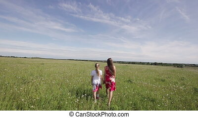 Young girls walking holding their hands