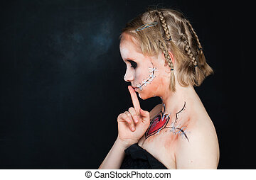 Young Girls with Love Makeup Holding her Finger to her Lips in a Gesture for Silence. Silent and Shushing
