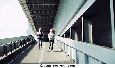 Young girls with smartwatch and smartphone running outdoors,...