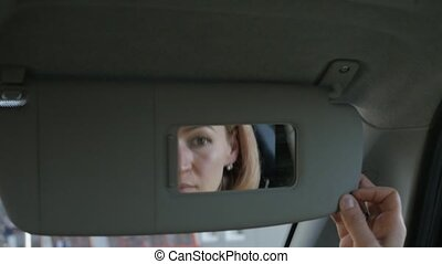 Young glamorous woman is fixing her makeup in a car looking...