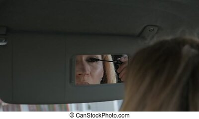 Young glamorous woman paints eyebrows in a car looking to...