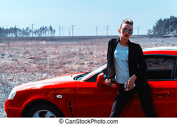 young glamour lady in mirror sunglasses looking at the camera near a red sports car
