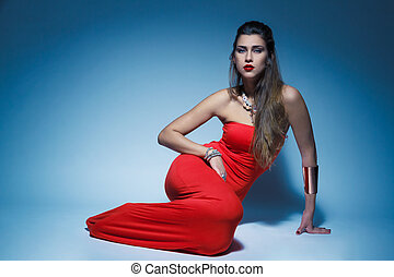 Young glamour woman in red dress long hair