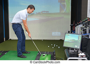 young golf player having playing video-game golf indoors