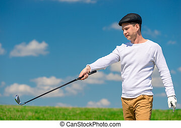 Young golfer in a cap and golf club on a green playing field