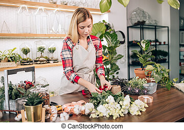 young good-looking florist woman in shop