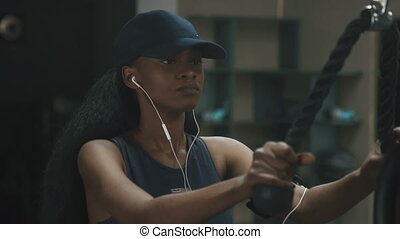 Young gorgeous african-american woman working out at the gym and listens to music in earphones