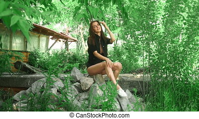 gorgeous lady in jacket on naked body sits on a rocks at the...
