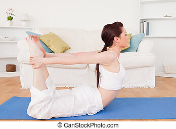 Young gorgeous red-haired female stretching in the living room