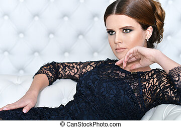 young gorgeous woman in black dress with beautiful make-up...