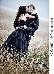 Young goth couple kissing outdoors. Contrast colors.