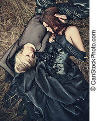 Young goth couple outdoors. Camera top view.