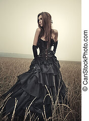 Young goth woman walking on field.