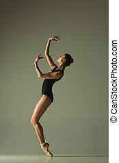 Young graceful female ballet dancer dancing in mixed light