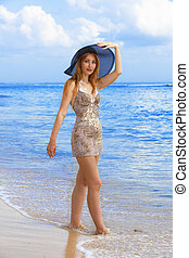 Young graceful woman on coast of ocean with hat