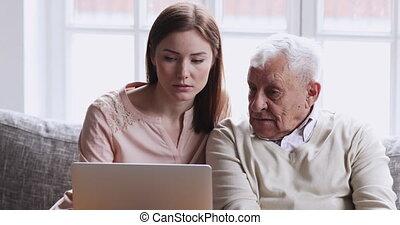 Young adult grown granddaughter, daughter or female carer teaching senior grandparent elderly man older grandad using laptop sitting on sofa in living room, old people learning computer concept