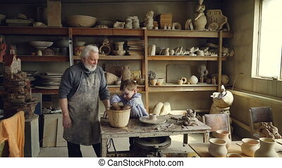 Young grandson is molding clayware in his grandfathers's studio while his loving senior grandpa is standing near him and watching him with love. Family traditions concept.