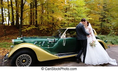 Young groom hugging and kissing  his beautiful white in front of a green retro car on the park.