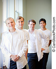 Young groom standing with groomsmen, getting ready for wedding