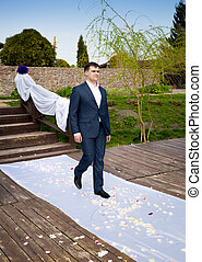 young groom walking during wedding ceremony to bride