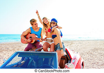 young group having fun on beach playing guitar