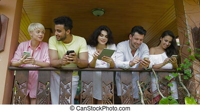Young Group Of Friends Using Modern Gadgets Messaging Stnd...