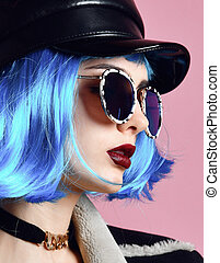 Young grunge style woman with blue wig hair in gold chain choker on neck and black leather hat