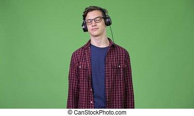 Young guilty teenage nerd boy listening to music - Studio...
