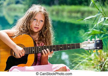 Young guitar student playing at lake.