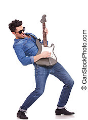 Full length image of a young guitar player performing very passionately on a white background