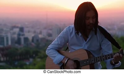 Young guitarist playing against a beautiful city landscape slow motion