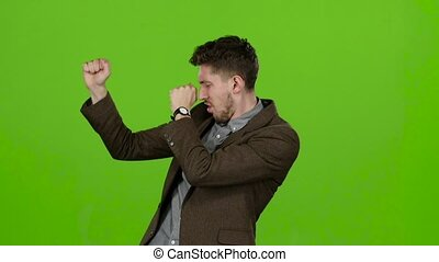 Young guy, a businessman, rejoices at his victories. Green screen. Slow motion