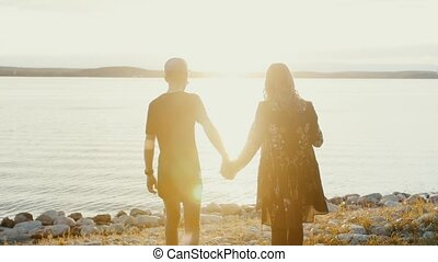 Young guy and girl couple in love go to the water's edge on rocky beach