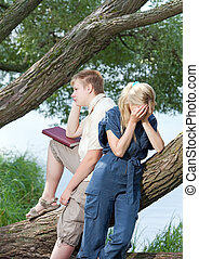 Young guy and girl with books on the nature near lake, quarrel