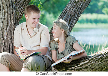 Young guy and girl with books on the nature near lake